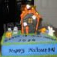 Hollow!! Marble cake with vanilla buttercream. Gumpaste ghost, royal icing fence and a gingerbread house in the center.