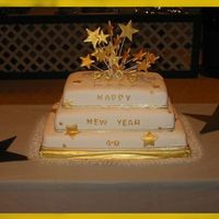 Welcome 2005 Happy New Year cake covered in white fondant. Stars on top made in run sugar and then painted with Gold luster dust. Stars attached to the...