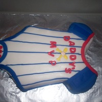 Baseball Onesie Carved chocolate cake filled with chocolate peanut butter buttercream.It is covered in Michelle Foster's fondant. I was told the...