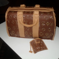 Louis Vouitton Purse Cake This cake is covered in Fondant with fondant details. The LV's are done with gold sparkle gel. :-)
