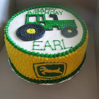 John Deere Cake This is just a layered round cake with a tractor freehanded and startipped on top and bigger star tips all around the side with the John...