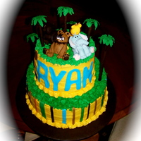 Jungle Safari Baby Shower Cake  12 in cake base, 8 inch cake on top. Cake board covered in brown fondant. Buttercream icing with fondant accents. Jungle animals made from...