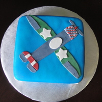 Airplane Single tier, double layer square cake covered in fondant and airbrushed blue. Flat fondant military style plane lying on top.
