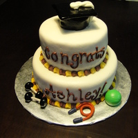 Exercise And Sports Science Theme Grad Cake Two tier cake covered in white fondant with maroon and gold piped edges. The topper is a grad cap made of cake, covered in fondant and...