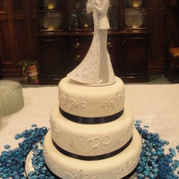 Navy And Ivory Wedding Cake Three tier vanilla wedding cake covered in ivory fondant. The piping is homemade buttercream with silver dragee accents. The ribbon around...