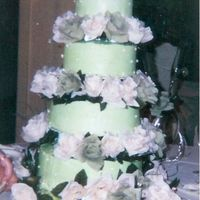 First Wedding Cake Bride wanted green and ivory cake to match her dress. Cake is BC with silk flowers. Cake wasn't tilted the photographer was LOL!