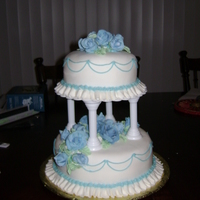 Blue Tiered Cake  The cake is strawberry and yellow covered in white fondant with a ruffle, blue string work and fondant roses and leaves. This is my final...