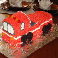 Firetruck Cake Chocolate cake carved into a firetruck with buttercream icing. I used Dots for the lights and oreos for the wheels.