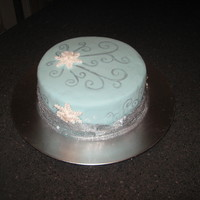 Winter Wonderland Chocolate cake with raspberry filling. Covered in mmf with gumpaste snowflakes, hand painted silver swirls and real silver ribbon around...