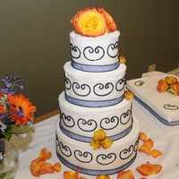 Navy Blue Scroll This cake had navy blue ribbon and piping with decorative pearl strand on edges. Navy blue is a hard color to get. The flowers added the...