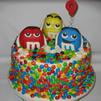 M&m Overload 10x4 inch chocolate cake with chocolate fudge filling, covered in BC and M&Ms...characters out of RKT and covered in MMF.
