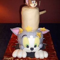 Tom & Jerry Cake I did this cake for a 6 yr. olds surprise birthday party. The cake was red velvet. Tom's head and the mallet are cake. Little Jerry...