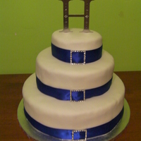 My First Wedding Cake White Cake, Raspberry Filling, Covered in Fondant, Blue Ribbon and BrochesMy first wedding cake, my 3rd time using fondant nad my first...