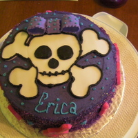 Girly Skull Cake Chocolate cake with chocolate filling, butter cream icing and chocolate guitars/music notes, fondant skull and bow, and sprinkles on the...