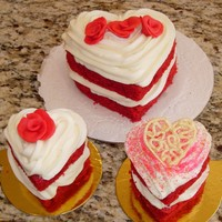 "Mini And Individual Red Velvet Heart Cakes a 5"" red velvet heart cake and 2 cupcake sized red velvet hearts. Sides are exposed for color and top designs vary."