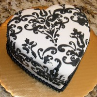 "Black And White Mini Damask Heart A small 5"" heart cake covered in white chocolate fondant and a black royal icing stenciled damask pattern."
