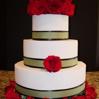 Modern Wedding buttercream icing, layered ribbons (black and green) and red flowers.