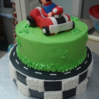 Mario Cake Vanilla Cake with BC. The car is Rice Crispy Treat covered with fondant and MMF as well as Mario.