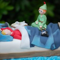 Peter Pan Dreams A cake for a little boy who loved Peter Pan. It has an open book and a torch on his pillow, with a 'dream' Peter Pan sitting on...