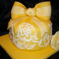 Yellow Spring Cake 6 inch cakes covered in white chocolate marshmellow fondant. Flowers around the sides of the cake through brush embroidery. Fondant bow and...