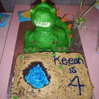 3D Dinosaur Cake With Drinking Hole And Fossils There were actually dinosaur bones on teh sides of the cake, that was left brown.