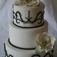 Black N White Magnolia Cake white fondant, black 3 d scrolls, finished off with magnolia flowers and simple leaves for a touch of color.