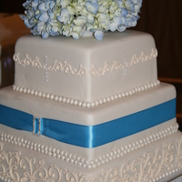 Ivory Scroll Ivory scroll on ivory fondant with blue trim and a rhinestone buckle. Blue fresh hydrangea topper.