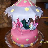 Merry-Go-Round Merry-go-round. round cake covered with MMF. Used sticks (that was covered) for the poles. The mother of the girl gave me the ponies.......