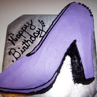 Purple Shoe Yellow cake with Buttercream frosting. shoe design was shaped by hand. Edible black sparkles line the bottom.