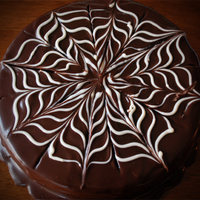 Chocolate Ganache Spider Web Cake Chocolate cake with raspberry sauce soaked into the layers. Vanilla custard filling and ganache over the top. White chocolate was used to...