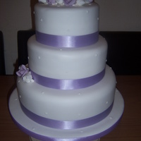3 Tier Wedding Cake With Lilac And White Flowers 3 tier stacked wedding cake with sugarpaste roses and ribbon