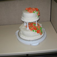 Wilton Course 3 Lemon flavored bottom tier and orange flavored top tier with butter cream filling and covered with fondant and fondant roses and leaves
