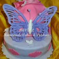 Butterflies And A Rose A 2-tiered cake with the top layer shaped and decorated to resemble a rose then decorated with a bunch of butterflies in all shapes and...