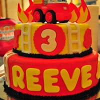 Reeve's 3Rd Birthday Cake Firefighter theme cake. It had red firetruck cut outs on the top tier and yellow fire hats around the bottom tier.
