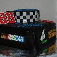 Nascar Cake Chocolate Cake covered in Chocolate Butter Cream accented with royal icing decals.