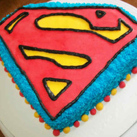Superman Superman cake made by baking cake in a 9/13 pan then cutting in half making a 2 layer cake in shape of emblem. the emblem made by layering...
