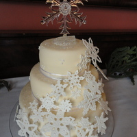 "Snowflake Wedding Cake a basic white almond wedding cake with blackberry filling. 12"", 9"" and 6"". Covered in mmf and Snowflakes are gumpaste. The..."