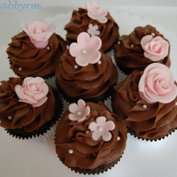 Chocolate Cupcakes With Pink Flowers Chocolate with chocolate buttercream. Sugar pearls. Pink fondant flowers.