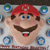 Mario Brothers Sculpted Mario and matching cupcakes. Fondant covered and details.