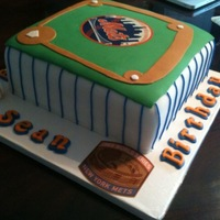 A Fan Of The Mets everything is edible except for the old stadium logo on the corner of the cake board