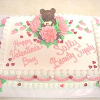 Valentines Bear this is a 9x13 cake, decorated with buttercream icing, and buttercream roses, a chocolate bears is snuggles in a cluster of roses, as candy...