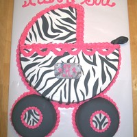 Zibra Babby Buggie this is a baby buggie made from a 16in round cake and (2) 6in round the 6in cakes are covered in black fondant and decorated with zibra and...