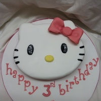 "Hello Kitty hello kitty face cake, carved from a 10"" round vanilla cake. covered with fondant,fondant bow and lettering. eyes and whiskers are..."