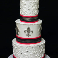 Silver Fleur De Lis Red and black fondant ribbons are touched with a hint of silver. The Fleur de lis are made using a mold. Very classy with a little wow.