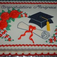 Graduation Cake   Cake frosted and decorated in buttercream with royal icing drop flowers.