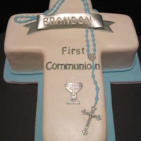 First Communion Cake This cake was inspired from a cake sent to me from Flicker. Cake is covered in fondant. Banner, words and rosary were done in Gum Paste.