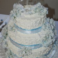 "Stacked 3-Tier Round This is scratch pound cake with butter cream icing, silk mums and plastic ""crystal"" doves."