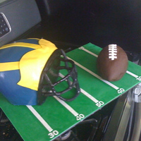 Michigan Football michigan helmet and football. helmet is all cake and the football in rice crispy treats. Face mask is a wire structure with fondant formed...
