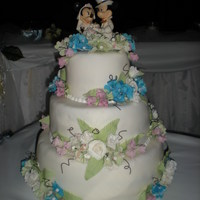 Disney Wedding White fondant covered with sugar flowers: blue and green hydrangea, white and pink roses, cake topper was purchased and provided by client...