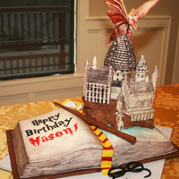 Harry Potter Themed Birthday Cake - Hogwarts Castle With Dragon Harry potter themed birthday cake. All edible materials. The castle is RKT and modeling chocolate, the dragon is gumpaste, the book is cake...